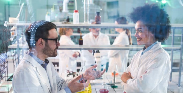 Two scientists discussing about research while working in laboratory. There are people in the background. The view is through glass.